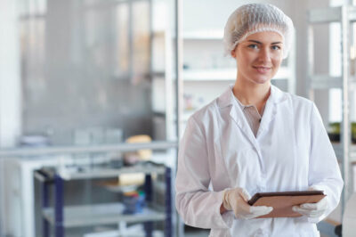 Waist up portrait of young female scientist holding digital tablet and smiling at camera while standing in medical laboratory, copy space